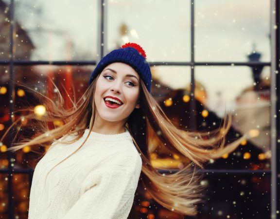 Street fashion portrait of smiling beautiful young woman playing with her long hair. Lady wearing classic winter knitted clothes. Model looking aside. Festive garland lights. Snowfall effect. Toned.
